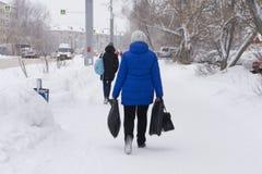 Den lyckliga kvinnan i blått omslag och solglasögon i härlig naturlig vinter parkerar medan fallande snö arkivfoton