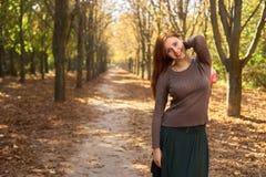 Den lyckliga kvinnan i hösten parkerar royaltyfri foto