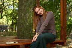 Den lyckliga kvinnan i hösten parkerar arkivfoto
