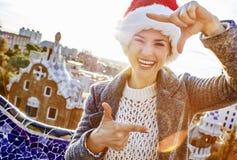 Den lyckliga kvinnan i jultomtenhatt på Guell parkerar med att inrama för händer Arkivfoto