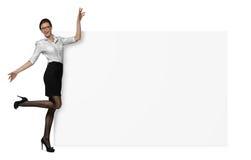 Den lyckliga kvinnan i officiella kläder rymmer en sida av ett tomt baner som isoleras på vit bakgrund Royaltyfri Bild