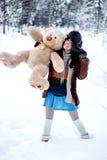 Den lyckliga kvinnan i pälslag och ushankaen med björnen på vit snö övervintrar bakgrund Arkivfoto