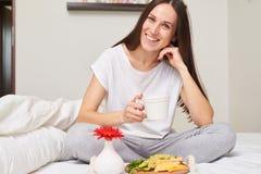 Den lyckliga kvinnan i pyjamas som tycker om den sunda frukosten, ler till hans Royaltyfri Bild