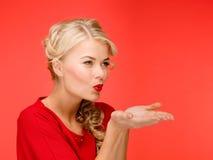 Den lyckliga kvinnan i röd klänning som blåser på, gömma i handflatan Fotografering för Bildbyråer