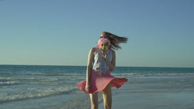 Den lyckliga kvinnan i rosa färgkjol med solglasögon går på stranden sniffar en blomma Den härliga flickan vänder på den tomma st arkivfilmer