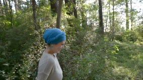 Den lyckliga kvinnan i turban kör på ett grönt gräs över skogen, slowmotion video stock video