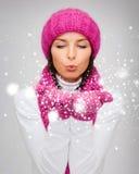 Den lyckliga kvinnan i vinterkläder som blåser på, gömma i handflatan Fotografering för Bildbyråer