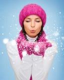 Den lyckliga kvinnan i vinterkläder som blåser på, gömma i handflatan Royaltyfri Foto