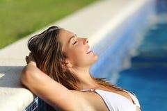 Den lyckliga kvinnan kopplade av i en simbassäng som tycker om semestrar Royaltyfri Fotografi