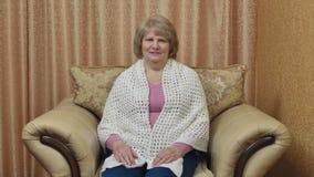 Den lyckliga kvinnan kopplar av i stolen efter en hård dag Gullig vuxen kvinna som är lycklig med liv som ler sammanträde i en st stock video