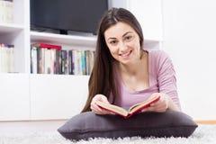 Den lyckliga kvinnan kopplar av och läseboken Royaltyfria Foton