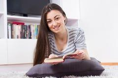 Den lyckliga kvinnan kopplar av och läseboken Fotografering för Bildbyråer