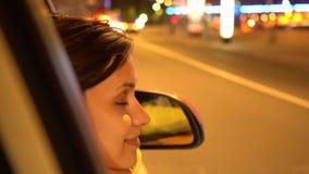 Den lyckliga kvinnan lutar ut fönstret för passageraresidobilen lager videofilmer