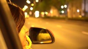 Den lyckliga kvinnan lutar ut fönstret för passageraresidobilen arkivfilmer