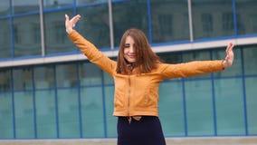 Den lyckliga kvinnan lyfter upp händer mot stads- landskap, omfamningstaden, vind, kopplar av arkivfilmer