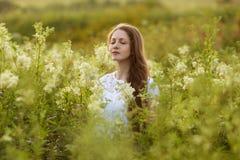 Den lyckliga kvinnan med ögon stängde sig bland vildblommorna Royaltyfri Foto