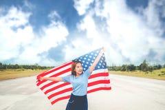 Den lyckliga kvinnan med amerikanska flaggan USA firar 4th Juli Royaltyfri Foto