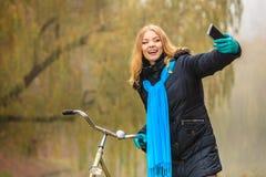 Den lyckliga kvinnan med cykeln parkerar in att ta selfiefotoet Arkivfoto