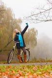 Den lyckliga kvinnan med cykeln parkerar in att ta selfiefotoet Royaltyfria Foton