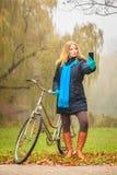 Den lyckliga kvinnan med cykeln parkerar in att ta selfiefotoet Royaltyfria Bilder