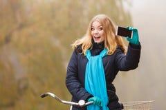 Den lyckliga kvinnan med cykeln parkerar in att ta selfiefotoet Arkivbilder