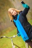Den lyckliga kvinnan med cykeln parkerar in att ta selfiefotoet Arkivfoton