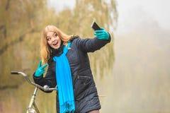 Den lyckliga kvinnan med cykeln parkerar in att ta selfiefotoet Royaltyfri Foto