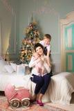 Den lyckliga kvinnan med ett nyfött barn i julen hyr rum en pram arkivfoton