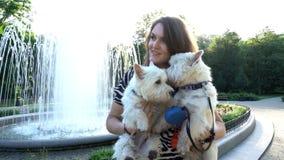 Den lyckliga kvinnan med hennes husdjurhundkapplöpning i händer nära springbrunnen i parkerar Handheld skott stock video