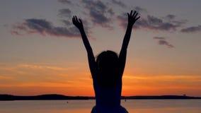 Den lyckliga kvinnan med hennes lönelyftarmar hoppar upp på den scharlakansröda solnedgången stock video