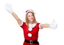 Den lyckliga kvinnan med jul klär med en välkommen kram för dig Arkivbild