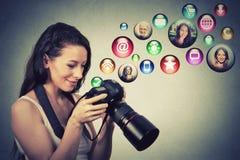 Den lyckliga kvinnan med kameran modellerar sociala massmediasymboler som flyger ut ur skärmen Arkivfoton