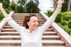 Den lyckliga kvinnan med lyftta händer som in står, parkerar Arkivbilder