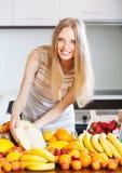 Den lyckliga kvinnan med melon och annan bär frukt Royaltyfria Foton
