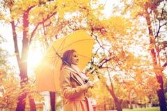 Den lyckliga kvinnan med paraplyet som går i höst, parkerar Arkivbilder