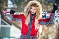 Den lyckliga kvinnan med skidar och poler Fotografering för Bildbyråer