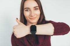 Den lyckliga kvinnan med smart klockavisning tummar upp Royaltyfria Bilder