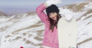 Den lyckliga kvinnan med snowboarden på skidar semesterorten arkivfilmer