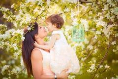 Den lyckliga kvinnan och barnet i den blommande våren arbeta i trädgården. Barnkissi royaltyfria foton