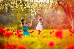 Den lyckliga kvinnan och barnet i den blommande våren arbeta i trädgården. Moderdag