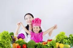 Den lyckliga kvinnan och dottern förbereder grönsaken Royaltyfri Bild