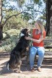 Den lyckliga kvinnan och hunden som in vilar, parkerar Fotografering för Bildbyråer