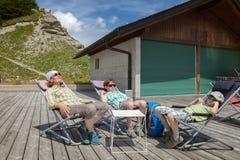 Den lyckliga kvinnan och två pojkar vilar på sommarterrase i vardagsrum royaltyfri foto