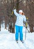 Den lyckliga kvinnan på argt skidar ridning på snow Fotografering för Bildbyråer