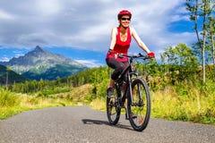 Den lyckliga kvinnan på cykeln tycker om den härliga naturen arkivfoto