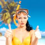 Den lyckliga kvinnan på stranden med tummar up tecknet Arkivbilder
