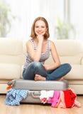 Den lyckliga kvinnan packar resväskan hemma Arkivbild