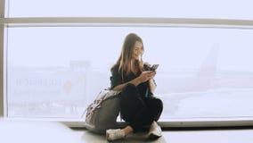 Den lyckliga kvinnan sitter med smartphonen vid flygplatsfönstret Caucasian flicka med ryggsäcken genom att använda budbäraren ap royaltyfri foto