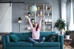 Den lyckliga kvinnan som är hemmastadd på soffan, kastar upp ett jordklot royaltyfria bilder