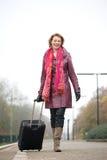 Den lyckliga kvinnan som ankommer på drevet, posterar Royaltyfri Bild
